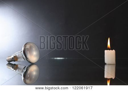 Blackout concept. One electric bulb against candle on dark background