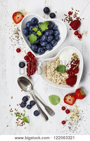 Healthy breakfast of muesli, berries with yogurt and seeds on white background -  Healthy food, Diet, Detox, Clean Eating or Vegetarian concept.
