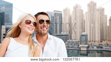 summer holidays, tourism, vacation, travel and dating concept - happy couple in shades over dubai city background