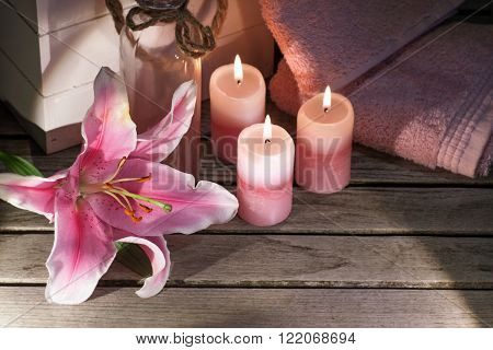 Candles with flower and towels on a wooden table