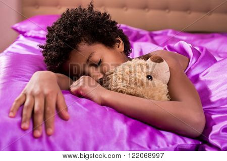 Afro boy sleeping with teddybear. Kid in bed with teddybear. Peaceful atmosphere of home.