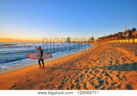 BARCELONA SPAIN - DECEMBER 30: Surfer with a board at dawn on the beach of Barcelona on December 30 2014. Barcelona is the secord largest city of Spain.