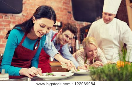 cooking class, culinary, food and people concept - happy couple and male chef cook cooking and decorating plates in kitchen