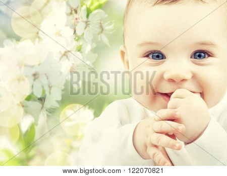 childhood, babyhood, summer, spring and health concept - closeup of happy baby boy or girl over green blooming garden background