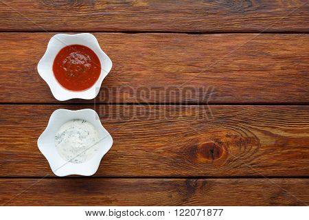 Food - ketchup and mayonnaise sauce. Two sauces at wood. Dip and dressing at wooden table. Pair of sauces top view. Flat lay. Tomato and sour cream sauces in white bowls.
