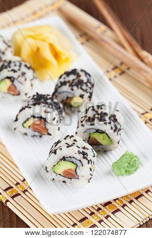 Uramaki sushi with avocado raw salmon and black sesame. Shallow dof