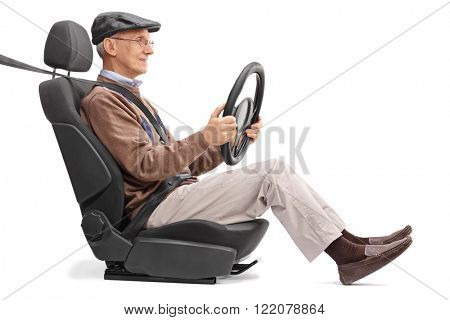 Senior holding a steering wheel seated on a car seat fastened with seatbelt isolated on white background