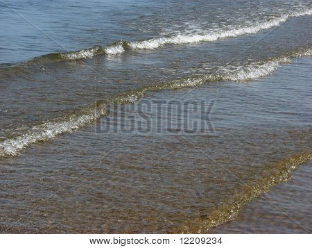 Wave pattern of sea as it laps gently on the shore.