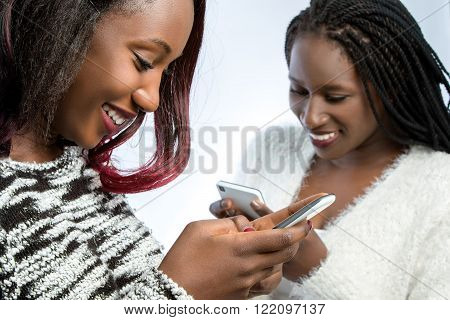 Close up portrait of two african teen girls playing on smart phones.Isolated on light background.