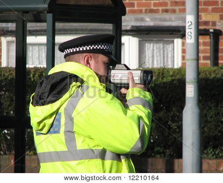 Policeman using hand held speed camera on UK road