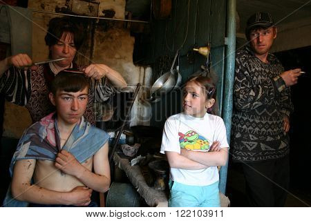 Lipovec village Tver region Russia - May 7 2006: Family Russian peasants in his home Mother cuts the hair son indoors kitchen in the presence of a parent and daughter.