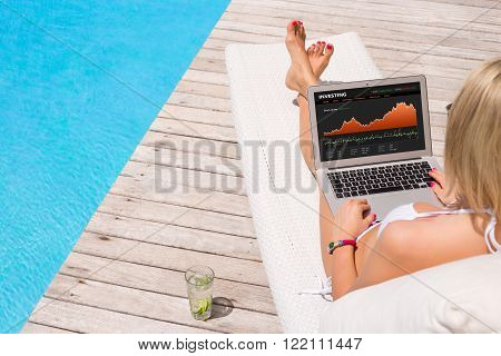 Business woman looking at investing website while lying by the pool