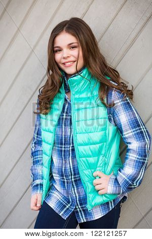 Cute fun and stylish caucasian tween girl outside against wall