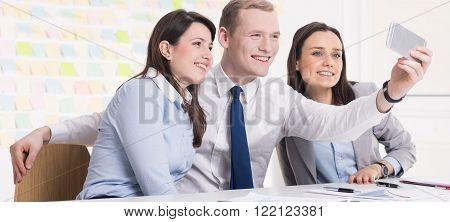 Picture of three workmates taking a selfie at the office