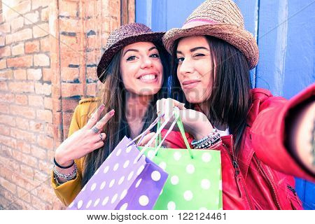 Cheerful women taking selfie with shopping bags - Young girlfriends having fun with self photo in old town - Concept of friendship and joyful youth - Soft vintage filter look with focus on right woman