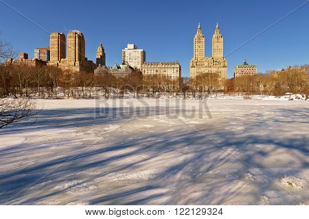 Sunrise on the frozen, snow covered Central Park Lake with view of the buildings of the Upper West Side, Manhattan. New York City