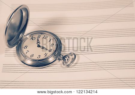 Pocket watch on a sheet of music paper (retro style, with copy space)