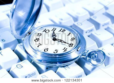 Ancient pocket watch on the computer keyboard (in blue tones)