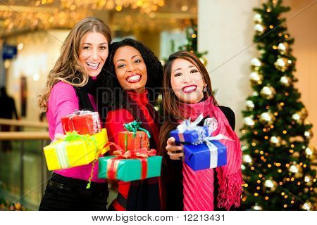 Group of three women - white, black and Asian - with Christmas presents in a shopping mall in front of a Christmas tree