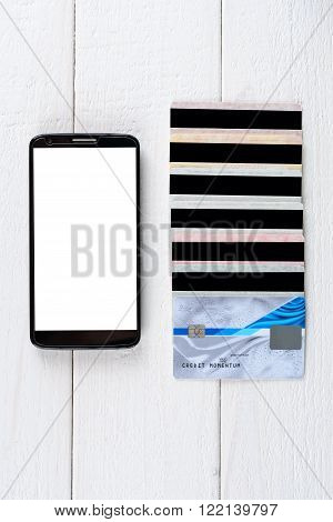 Credit Cards And Smartphone Lying On A Wooden Table