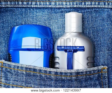 Mens cosmetics. Antiperspirant deodorant, aftershave lotion and disposable razor in jeans pocket. Basic skin care cosmetic products and accessories for men. Toiletry and cosmetic travel kit
