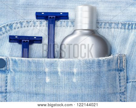 Aftershave lotion and disposable razors in shabby pocket of blue jeans. Shaving cosmetic products and accessories for men. Travel kit of toiletries and cosmetics