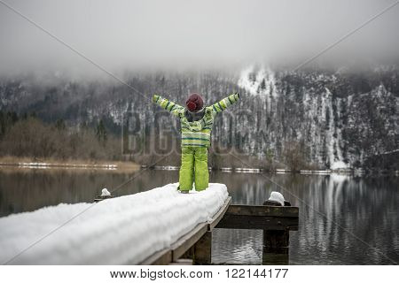 Toddler in green winter suit standing at the end of a snow covered pier on a lake with his arms outstretched towards beautiful winter nature.
