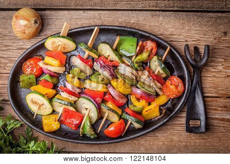 Vegetable skewers on a cast iron skillet.