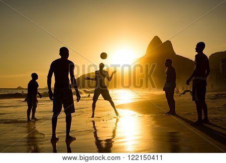 Rio de Janeiro, Brazil - Circa February 2016: Silhouette of locals playing ball at sunset in Ipanema beach, Rio de Janeiro, Brazil.