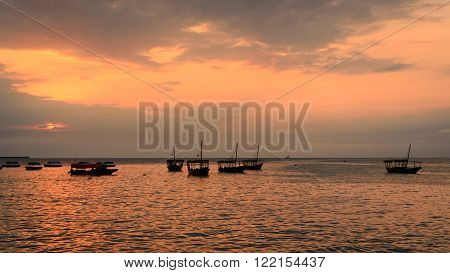 Colorful horizontal photo of traditional dhow boats on open sea on Indian Ocean close to Stone Town on Zanzibar Tanzania in East Africa at orange sunset.