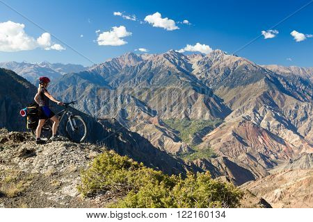 Bicycle traveler with loaded bike standing at cliff and enjoying view of mountains. Pontic mountains, Turkey