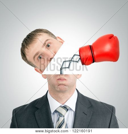 Boxing glove beating from businessmans head on grey background