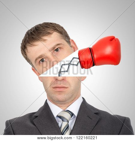 Boxing glove beating from businessmans head on grey background, closeup