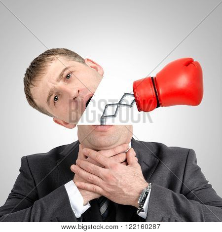 Boxing glove beating from businessmans head on grey background, close up view