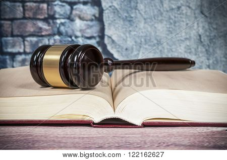 judges gavel and  book on wall background