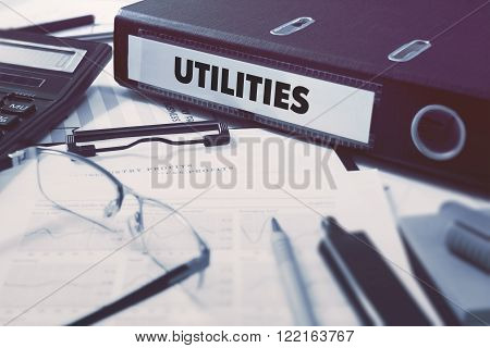Utilities - Ring Binder on Office Desktop with Office Supplies. Business Concept on Blurred Background. Toned Illustration.