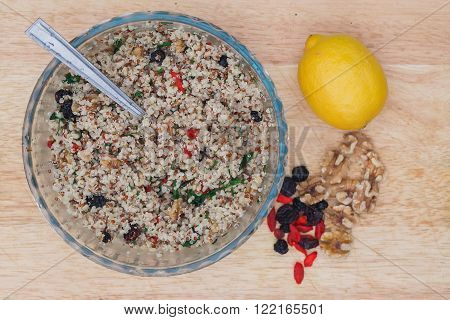 A bowl of delicious fresh quinoa and bulgar weat with parsley walnuts goji berries and blue berries sprinked with olive oil and lemon juice