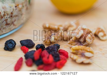 Ingredients for a salad with delicious fresh quinoa and bulgar weat with parsley walnuts goji berries and blue berries sprinked with olive oil and lemon juice