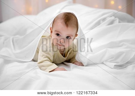 Loving baby lying under white blanket on soft bed, close up
