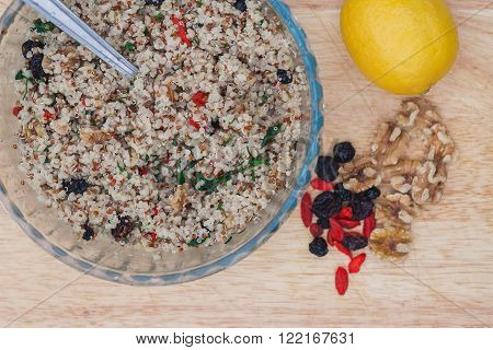 A bowl of delicious fresh quinoa and bulgar weat with parsley walnuts goji berries and blue berries sprinkled with olive oil and lemon juice