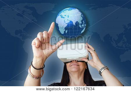 A woman touching a worldmap while enjoying a 3d experience. Vr headset is a gadget to use with a mobile phone