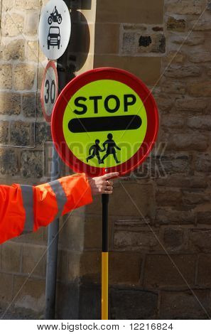 Lollipop lady holds stop sign to allow children to cross road