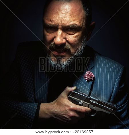 Mister with silver gun, portrait of a middle age man.