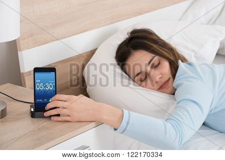 Woman Lying On Bed Snoozing Alarm On Mobile Phone poster