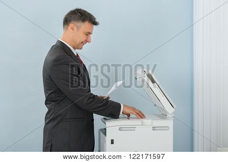 Businessman Keeping Paper On Photocopy Machine In Office