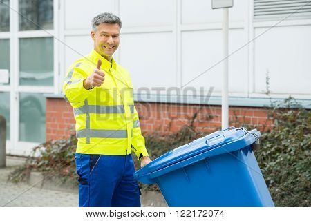 Mature Happy Working Man Holding Dustbin On Street