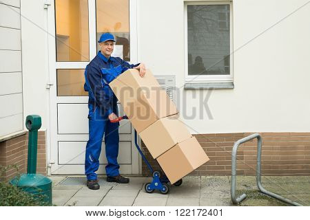 Delivery Man Holding Boxes On A Hand Truck