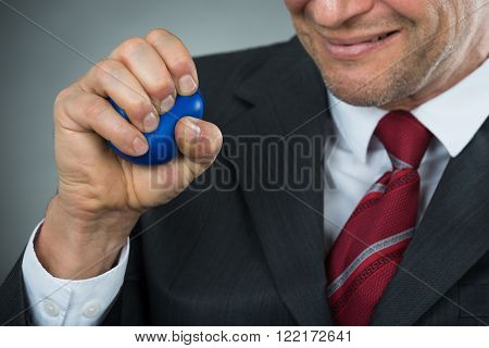 Businessman Pressing Stressball In Hand Over Black Background