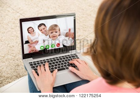Close-up Of Businesswoman Video chatting With Family At Home