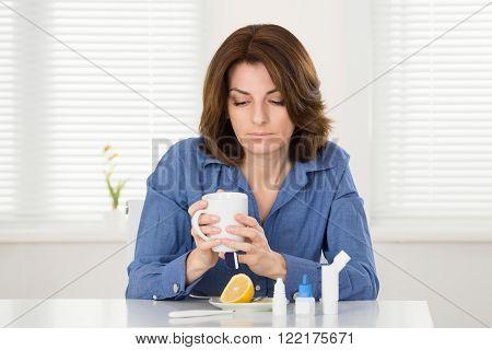 Sick Woman Drinking Lemon Tea In Office
